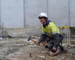 Naylor Love apprentice builder James ``Mouse'' Riach, of Dunedin, hammers in a peg on a building...