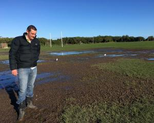 Saddle Hill Community Board chairman Scott Weatherall inspects a muddy section of a rugby field...