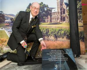 University Chancellor Dr Royden Somerville places the stone plaque to commemorate the opening of...