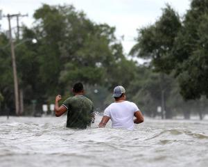 People wade through a flooded street after Hurricane Barry in Mandeville, Louisiana. Photo: Reuters