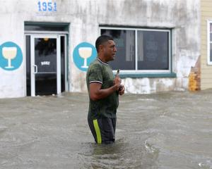 A man wades through a flooded street after in Mandeville, Louisiana. Photo: Reuters