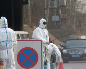 Workers in protective suits are seen at a checkpoint on a road leading to a village near a farm...