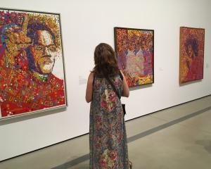 A woman examine's Wadsworth Jarrell's Black Prince, a portrait of Malcolm X, and other Jarrell...