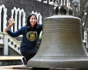 Human nutrition PhD candidate Claudia Leong prepares to give the University of Otago bell a whack...
