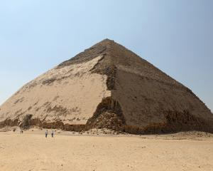 People walk in front of the Bent Pyramid of Sneferu, that was reopened after restoration work, in...
