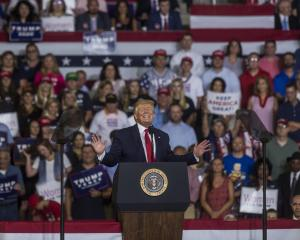 "Trump grins during a rally in North Carolina in which his supporters chanted ""send them back"",..."