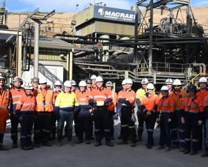 Oceana Gold employees gather with the gold bar containing the five-millionth ounce of gold, which...