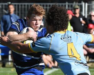Kaikorai first five-eighth Ben Miller fends University lock Ben Reidy during a premier game at...