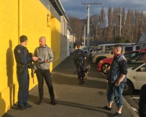 An armed police officer takes statements outside the Dunedin Art School. Photo: George Block