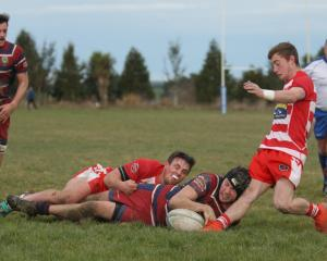 Jordan Willocks scores a try for Clutha Valley despite the efforts of Clutha fullback Zak Thoms....