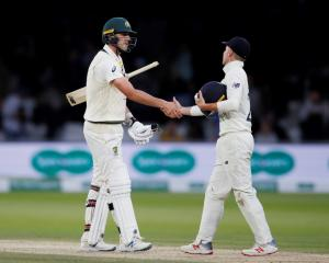 Australia's Pat Cummins and England's Rory Burns shake hands at the end of play as the second...