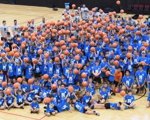 Youngsters and Steven Adams gather at a basketball camp held at ILT Stadium Southland yesterday....