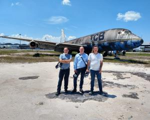 Wanaka Transport and Toy Museum owner Jason Rhodes (centre) in front of the former Air New...