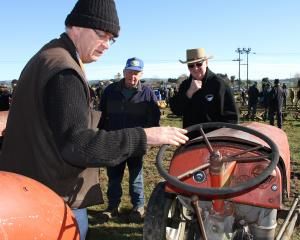Reminiscing about their days as young men driving tractors on farms are (from left) Rodger...