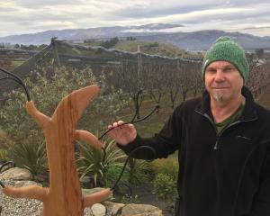 Sculptor Jim Ashe showcases one of his latest creations, made from recycled rimu bed frames....
