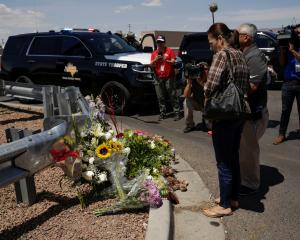 People look at flowers placed at the site of a mass shooting where 20 people lost their lives at...