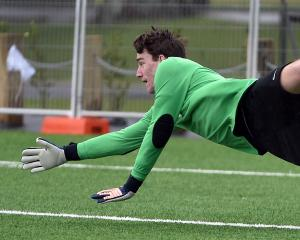 Otago University goalkeeper Stewart Catto attempts to save a Coastal Spirit shot during a...