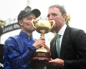 Rider Kerrin McEvoy and trainer Charlie Appleby pose with the cup after winning it with Cross...
