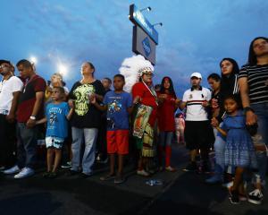 Children and adults gather outside the El Paso Walmart where a white supremacist gunman killed 22...