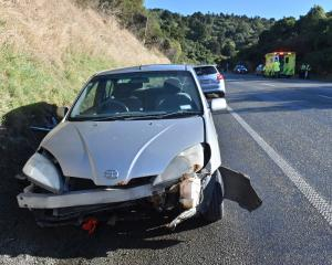 An ambulance attends the scene of two crashes on the Northern Motorway, Dunedin near the Pigeon Flat summit. Photo: Linda Robertson