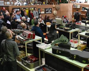 The steady tones of auctioneer John More help to empty shelves filled with musical memorabilia....