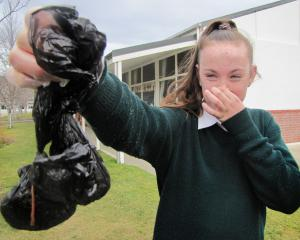 St Gerard's School council leader Hannah O'Connor (13) holds up a couple of the bags of dog...