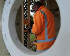 Downer staff member Garth Woodcock works to repair damage to the Elderslie summer house in the...