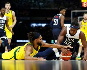 Patty Mills and Myles Turner compete for a loose ball during Australia's recent win over the US...