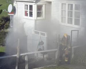 Dunedin firefighters battle a blaze on Puketai St. Photo: Gregor Richardson