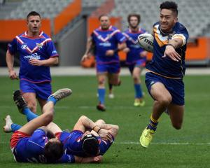 Otago Whalers back Willie Time smashes through two Tasman players during a match at Forsyth Barr...