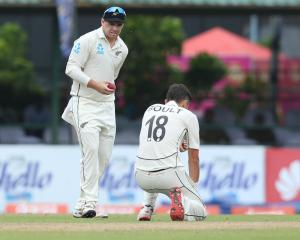 Tom Latham (left) and Trent Boult react after a dropped catch by Boult during the day two of the...