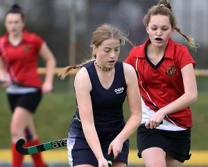 Otago Girls' High School hockey player Tessa Buschl (18), of Outram, dribbles a ball while being...