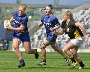 Otago Spirit centre Greer Muir tries to elude Wellington hooker Rosier Stirling while Spirit lock...