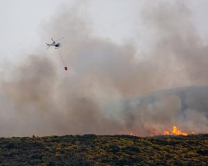 A helicopter battles a blaze on Flagstaff. Photo: Ruth Topless