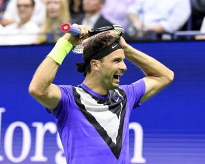 Grigor Dimitrov celebrates after winning his US Open quarterfinal match against Roger Federer....