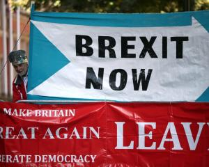A crown-wearing pro-Brexit demonstrator stands next to banners in London last week. Photo: Reuters