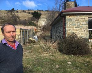 St Bathans property owner Tony Ward stands outside his historic cottage in the Central Otago town...
