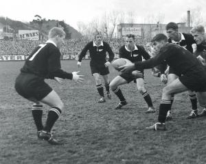 Colin Meads passes the ball to halfback Chris Laidlaw during a test between the All Blacks and...