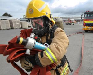 Firefighter Taine Michie, of Balclutha, carries hoses into the Silver Fern Farms Finegand plant...