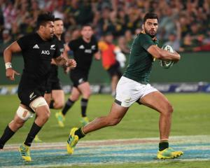 Damian de Allende on the run for the Springboks against the All Blacks last year as Ardie Savea...