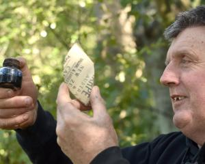 Dunedin military researcher Peter Trevathan holds an ink bottle and a piece of stoneware...