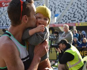 Inkster-Baynes kisses daughter Indi (3) after winning the national half marathon title.