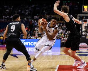 Giannis Antetokounmpo takes the ball to the hoop against Rob Loe as Corey Webster watches on....