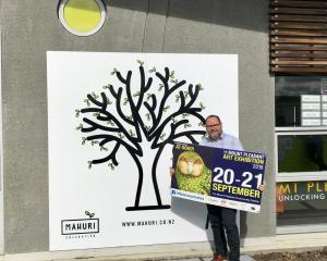 Mt Pleasant School principal Chris Nord stands next to the Mahuri tree, holding a poster for the...