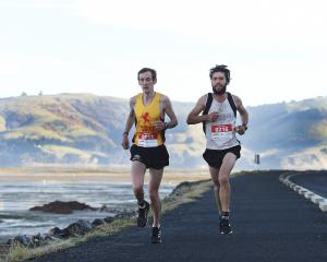 Runners Matthew Moloney (left) and Jonah Smith run past Harwood in the Dunedin Marathon yesterday...