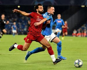 Mohamed Salah of Liverpool with Mario Rui of SSC Napoli contest the ball in this morning's...