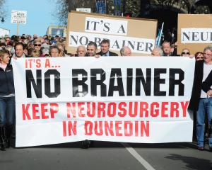 Marchers hold up a signs during a protest to keep neurosurgery services in Dunedin. Photo: ODT files