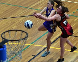 Dunedin Gold wing attack Mikayla Thorn and Eastern Southland wing defence Hope Rae compete for...