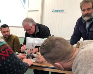 A team effort fixing a sewing machine at the Paekakariki repair cafe. Photos: Rachel Benfield