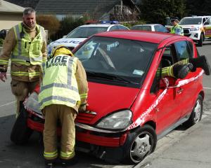 Emergency services at the scene of a crash where a car tipped on to its side in McBride St,...